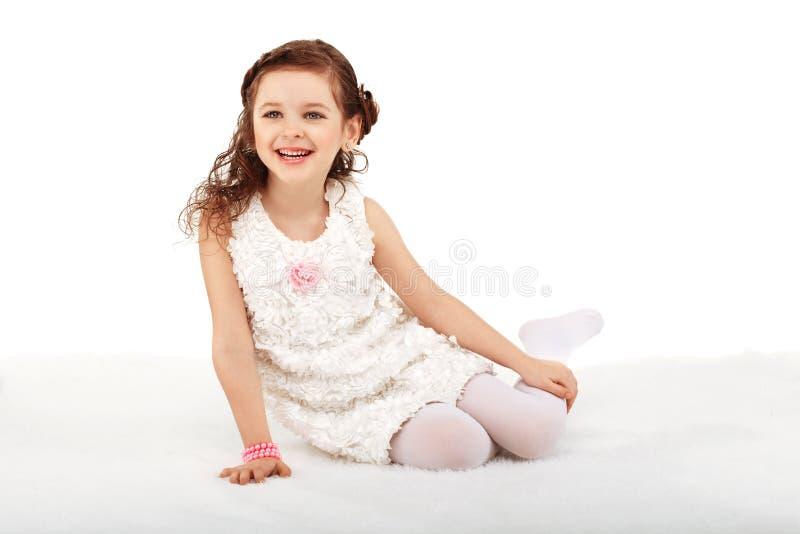 Porträt eines recht wenigen Spaßmodemädchens, das auf einem flaumigen sitzt lizenzfreie stockfotos