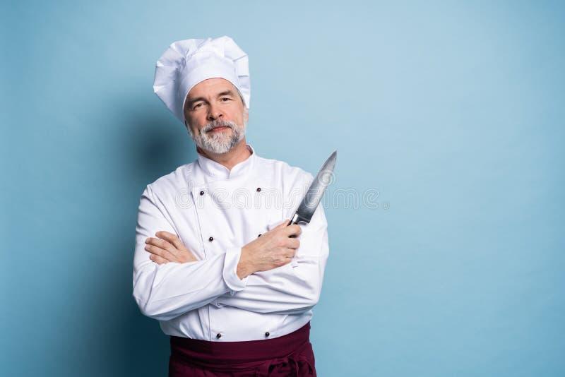 Porträt eines reifen Chefkochs, der Messer auf einem blauen Hintergrund hält stockfotos
