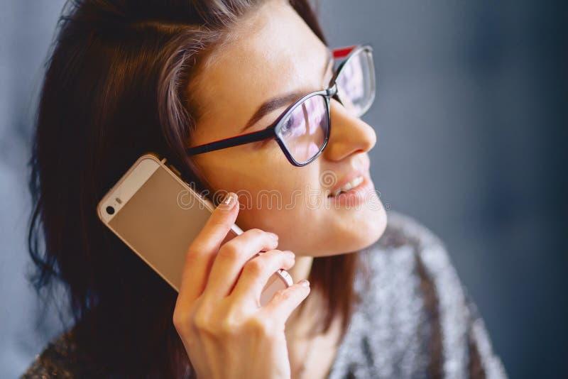 Porträt eines reizend Mädchens in den Gläsern mit einem Telefon lizenzfreie stockbilder