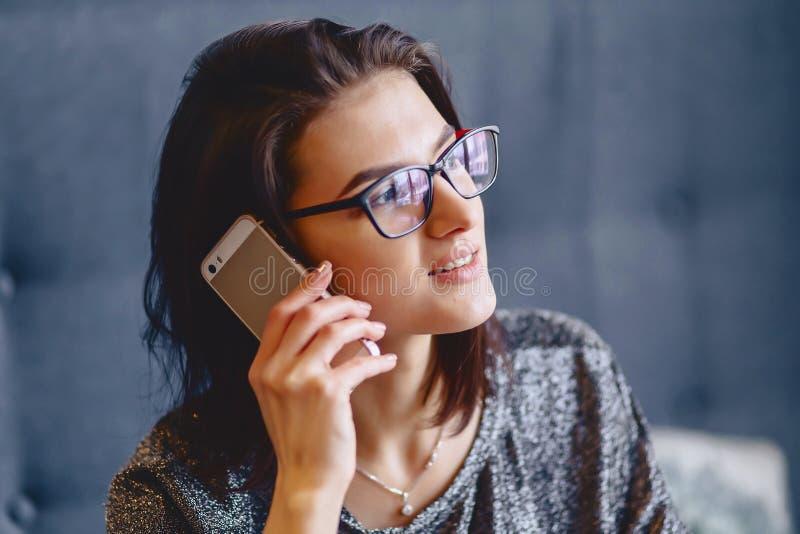 Porträt eines reizend Mädchens in den Gläsern mit einem Telefon stockbilder
