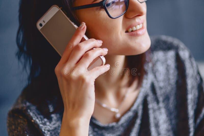 Porträt eines reizend Mädchens in den Gläsern mit einem Telefon lizenzfreie stockfotografie