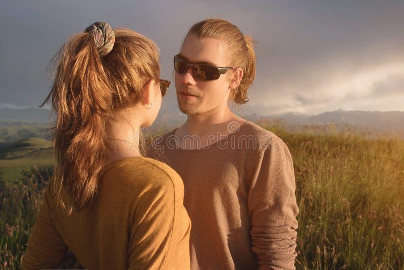Porträt eines romantischen jungen Paares in der Natur Ein Mann und ein Mädchen in der Sonnenbrille betrachten einander mit lieben lizenzfreies stockfoto