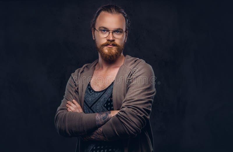 Porträt eines Rothaarigehippie-Mannes kleidete in der zufälligen Kleidung mit den Gläsern und Vollbart an und stand mit den gekre lizenzfreies stockfoto