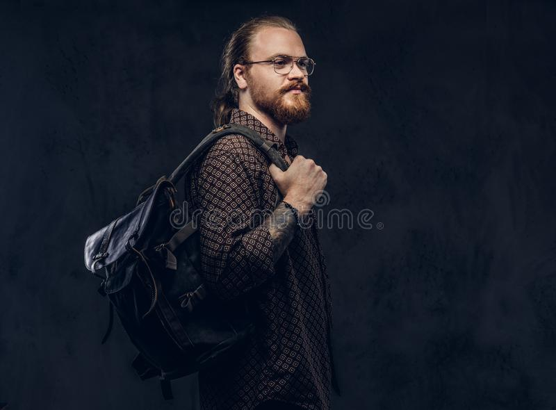 Porträt eines Rothaarigehippie-Studenten in den Gläsern gekleidet in einem Braunhemd, Griffe ein Rucksack, werfend an einem Studi lizenzfreies stockbild