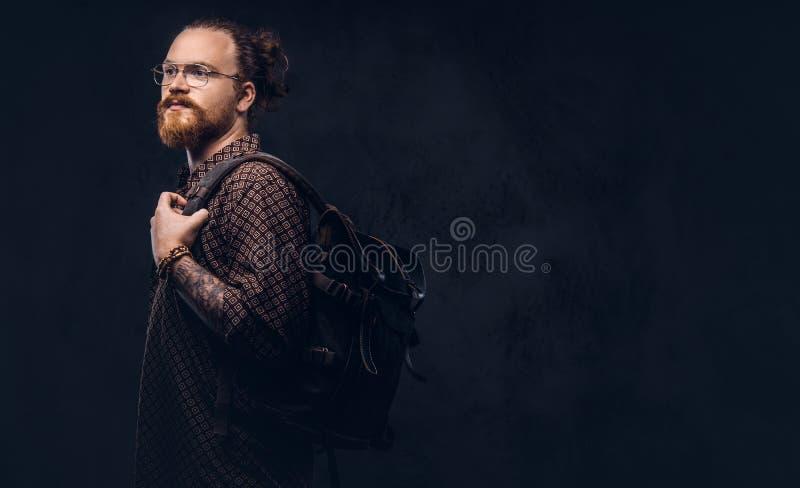 Porträt eines Rothaarigehippie-Studenten in den Gläsern gekleidet in einem Braunhemd, Griffe ein Rucksack, werfend an einem Studi stockfoto