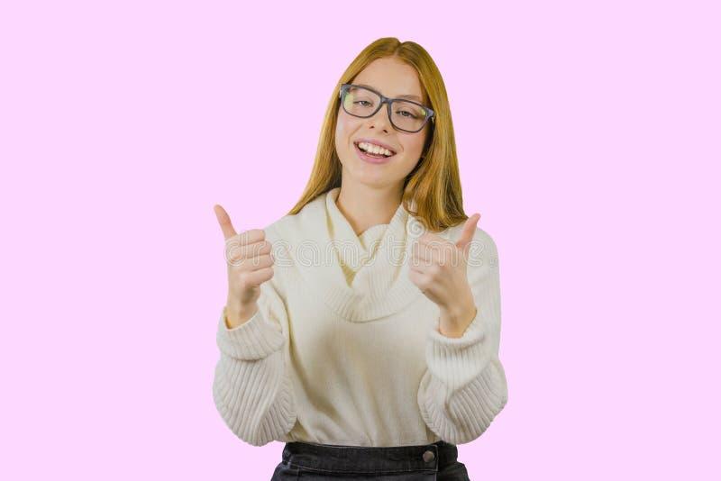 Porträt eines rothaarigen Mädchens in den Gläsern und in einer weißen Strickjacke, die die Klasse mit beiden Händen auf lokalisie lizenzfreie stockfotos