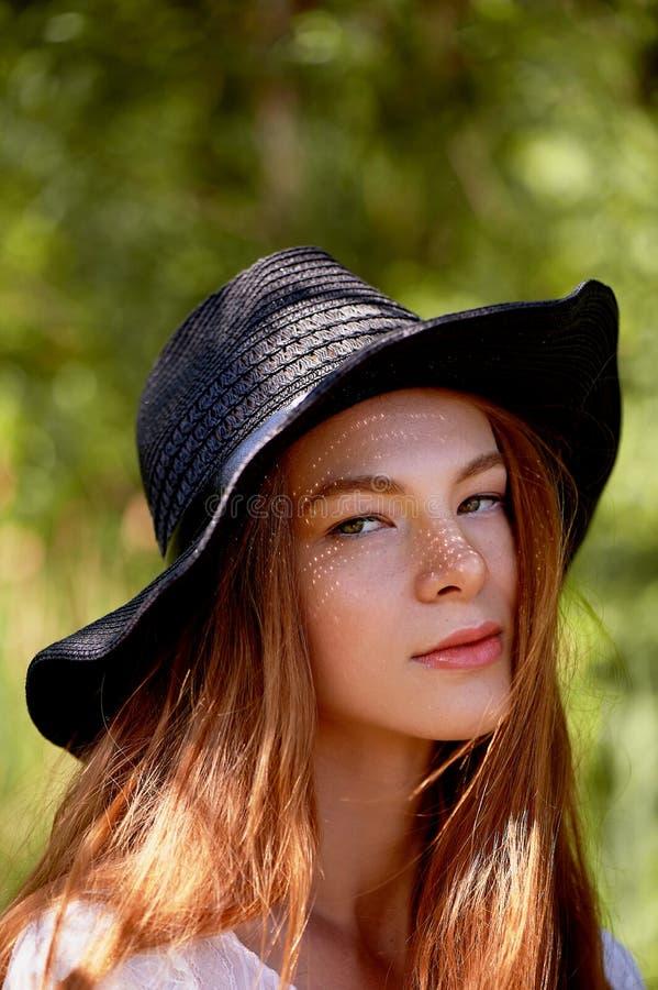 Porträt eines rothaarigen Mädchens mit dem langen Haar, in einem schwarzen breitrandigen Hut Die Sonne macht Sommersprossen auf d lizenzfreie stockfotografie