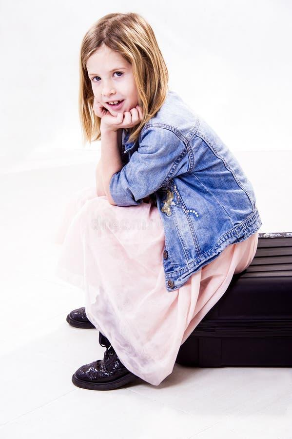 Porträt eines süßen kleinen Mädchens ist, denkend sitzend und auf einem Koffer lizenzfreie stockbilder