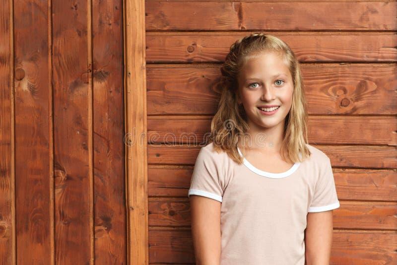 Porträt eines süßen Teenagers Sommermode Mädchen mit blondem Haar, schönes Gesicht und perfektes Lächeln, über Holzboden Kopieren lizenzfreie stockfotos