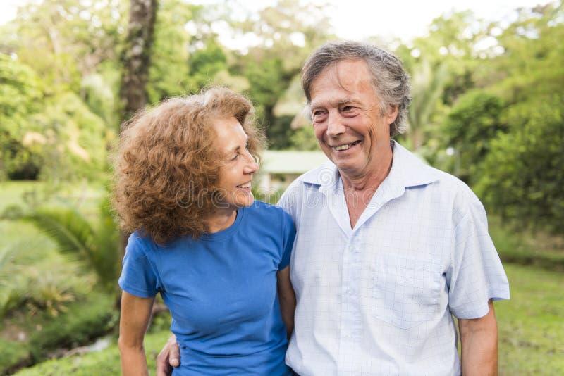 Porträt eines schönen älteren Paares, das draußen umfassend steht stockfotografie