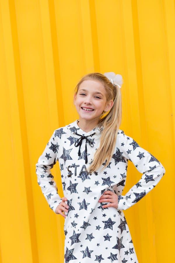 Porträt eines schönen blonden Mädchens auf einem gelben Hintergrund stockfotos