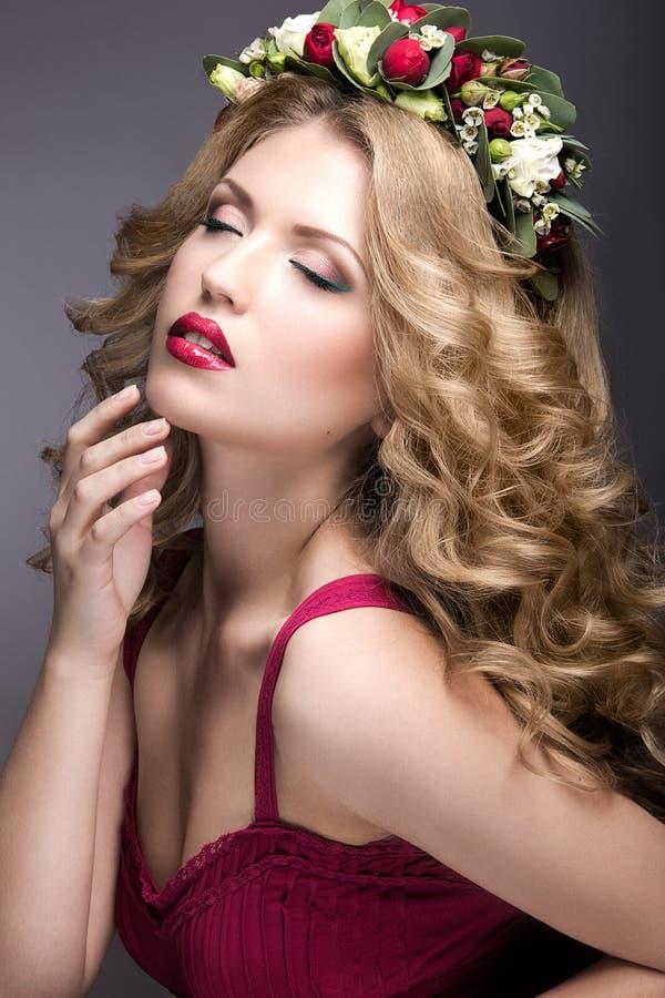 Porträt eines schönen blonden Mädchens mit Locken und des Kranzes der purpurroten Blumen auf ihrem Kopf Schönes lächelndes Mädche stockbilder