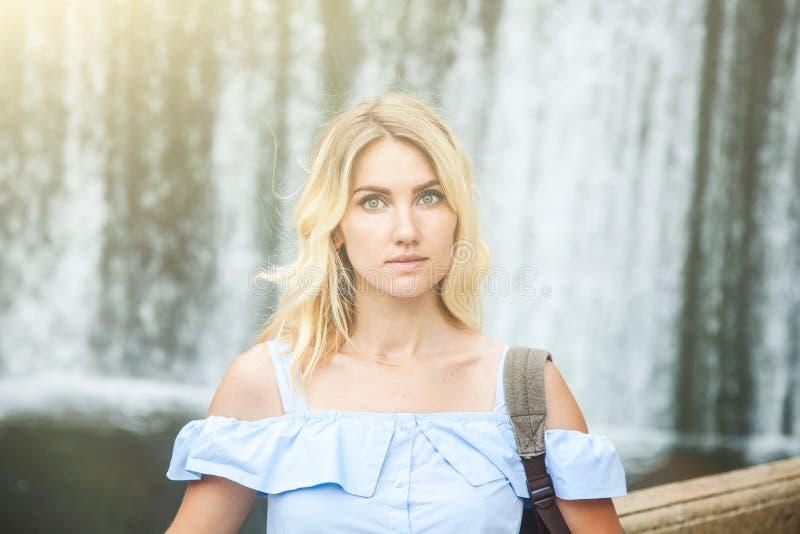Porträt eines schönen blonden Mädchens nahe einem Wasserfall Reisemädchen lizenzfreie stockbilder
