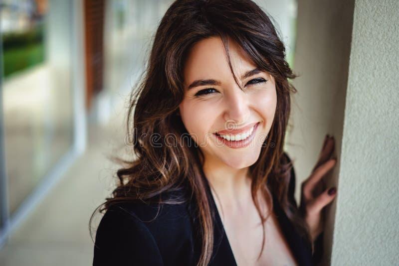 Porträt eines schönen Brunette, der durch die Wand lacht lizenzfreies stockfoto