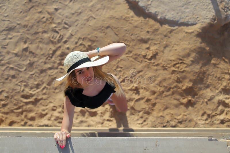 Porträt eines schönen gebräunten sexy Mädchens auf dem Strand Frau, die im Badeanzug auf dem Sand sich entspannt Reisenkoffer mit stockbilder