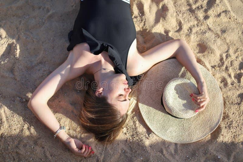 Porträt eines schönen gebräunten sexy Mädchens auf dem Strand Frau, die im Badeanzug auf dem Sand sich entspannt Reisenkoffer mit lizenzfreie stockfotografie