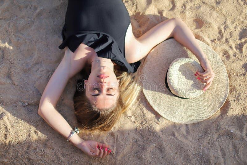 Porträt eines schönen gebräunten sexy Mädchens auf dem Strand Frau, die im Badeanzug auf dem Sand sich entspannt Reisenkoffer mit stockbild