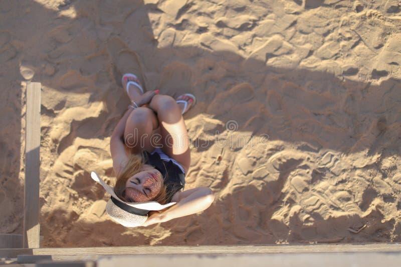 Porträt eines schönen gebräunten sexy Mädchens auf dem Strand Frau, die im Badeanzug auf dem Sand sich entspannt Reisenkoffer mit stockfotos
