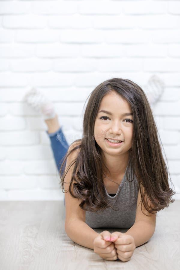 Porträt eines schönen glücklichen lächelnden Mädchenrestes auf dem Boden lizenzfreies stockfoto