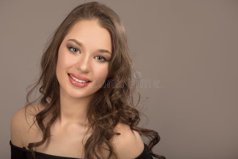 Porträt eines schönen jungen Brunette mit dem langen gewellten Haar lizenzfreie stockbilder