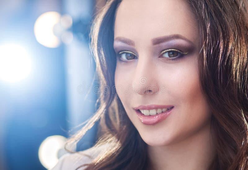 Porträt eines schönen jungen Brunettemädchens mit dem gelockten Haar, das angewandtes Make-up war lizenzfreies stockfoto