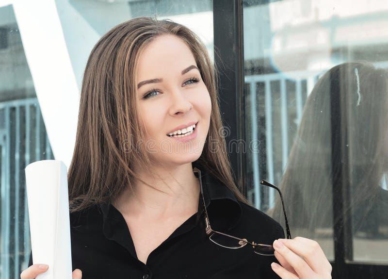 Porträt eines schönen jungen Ingenieurmädchens, das ein Blatt Papier und Gläser hält, glücklich, das Projekt abzuschließen lizenzfreies stockbild