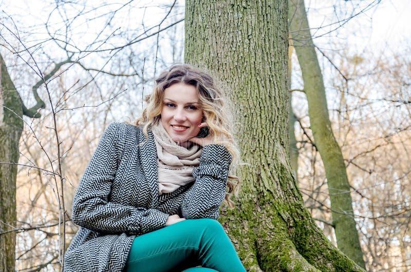 Porträt eines schönen jungen jungen Mädchens in einem Mantel, der auf Natur nahe einem Baum im Park sitzt stockbild