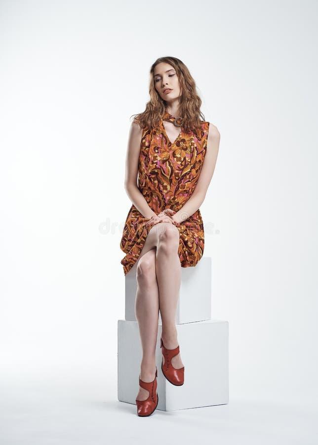 Porträt eines schönen jungen Mädchens, das auf einem weißen Würfel sitzt stockfotos