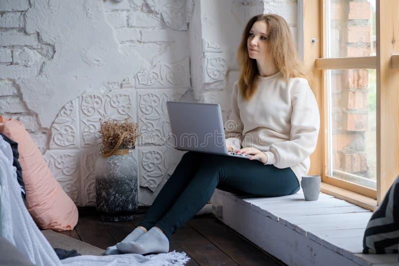 Porträt eines schönen jungen Mädchens, das morgens auf dem Fensterbrett mit einem Laptopbuch und einem Getränkkaffee sitzt stockbilder