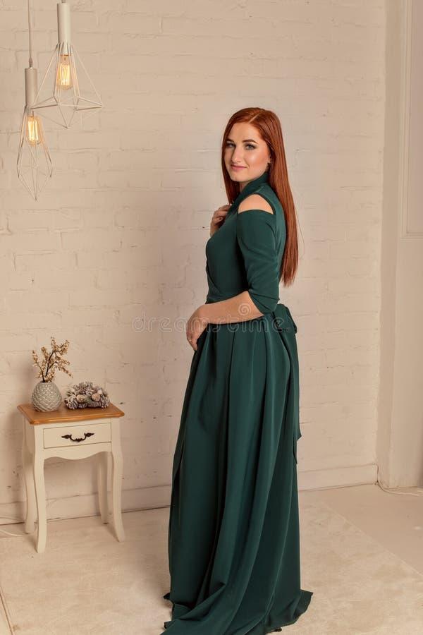 Porträt eines schönen jungen Mädchens in einem grünen Abendkleid am hellen Innenraum lizenzfreies stockfoto
