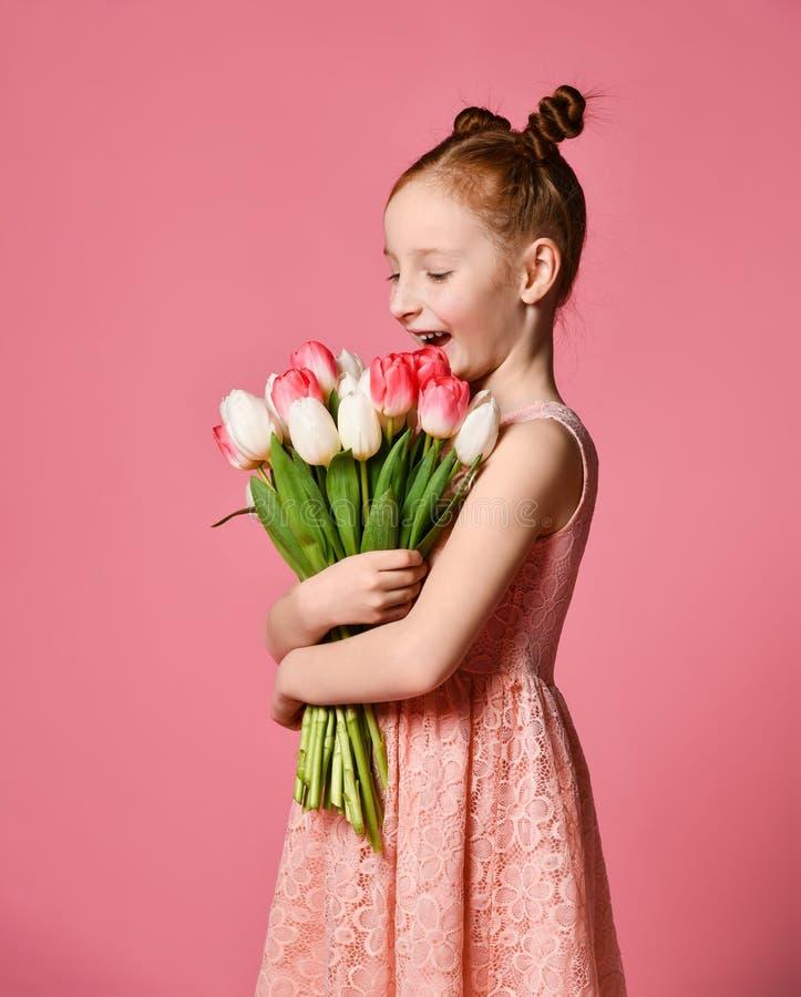Porträt eines schönen jungen Mädchens im Kleid, das großen Blumenstrauß der Iris und der Tulpen lokalisiert über rosa Hintergrund stockbild