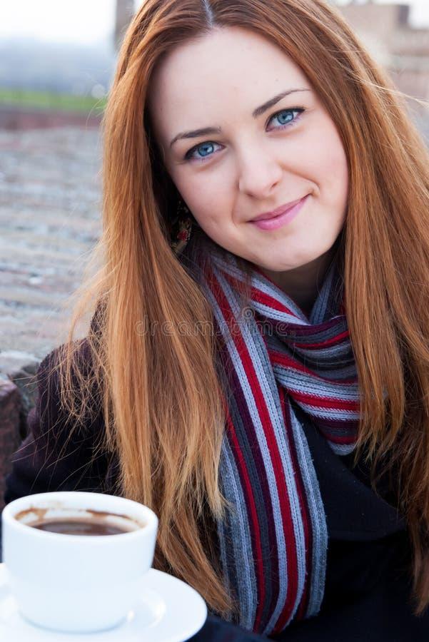 Porträt eines schönen jungen Mädchens mit dem roten Haar und den blauen Augen Kaffee trinkend stockfoto