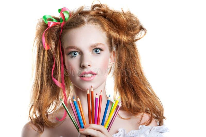 Porträt eines schönen jungen Mädchens mit farbigen Bleistiften in der Hand Mädchen mit kreativer Frisur und dem Make-up, die Blei stockfotografie