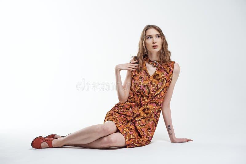 Porträt eines schönen jungen Mädchens sitzt auf dem weißen Boden und schaut oben in der Überraschung lizenzfreies stockbild