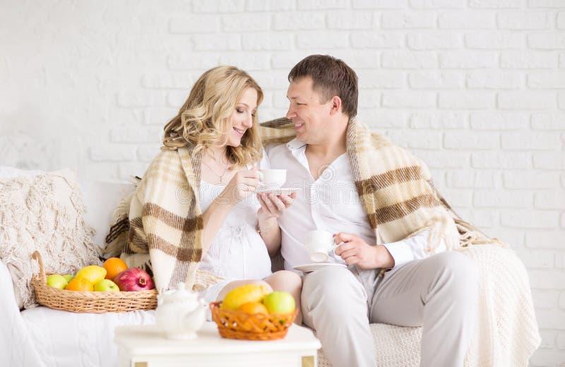 Porträt eines schönen jungen Paares, schwangeres Mädchen, das zu Hause Plaid bedeckend frühstückt stockbild