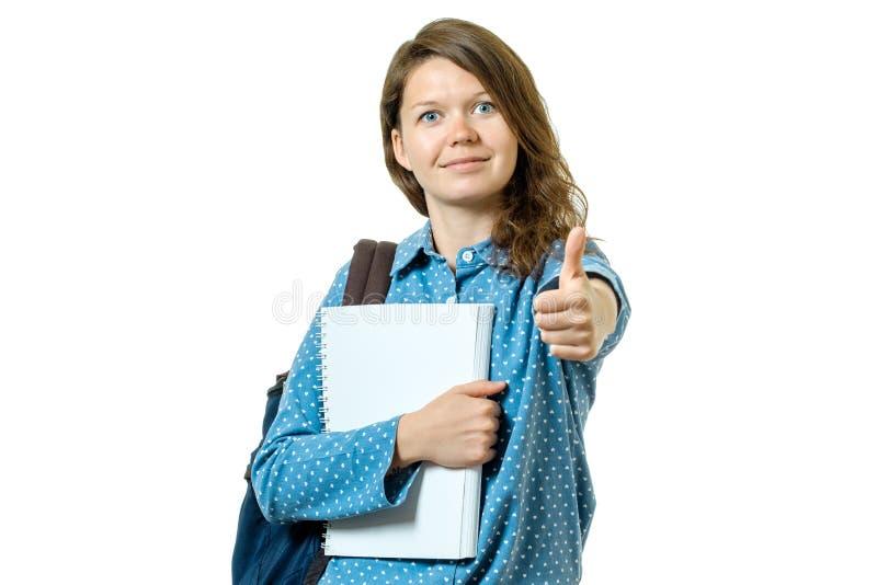 Porträt eines schönen jungen Studentenmädchens, das sich Daumen zeigt stockfotografie