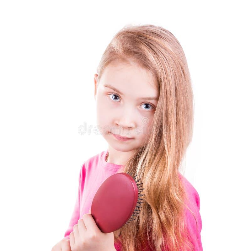 Porträt eines schönen kleinen Mädchens, das ihr langes Haar bürstet. Haarpflegekonzept. lizenzfreies stockbild