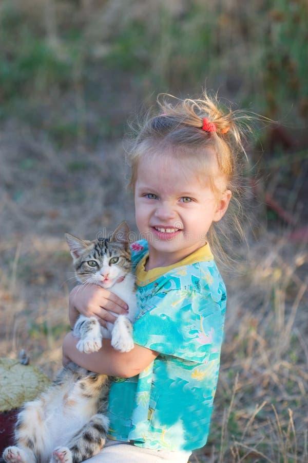 Porträt eines schönen kleinen Mädchens mit einem Kätzchen stockbild