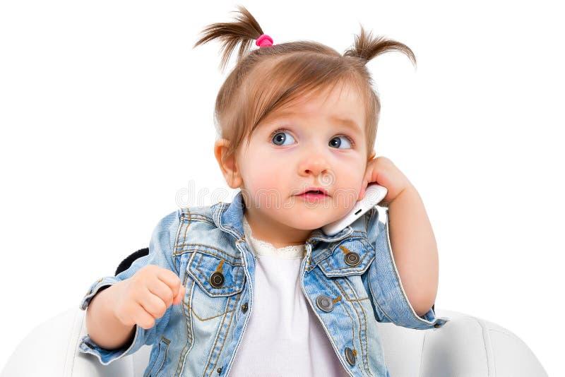 Porträt eines schönen kleinen Mädchens, sprechend am Telefon stockfotos