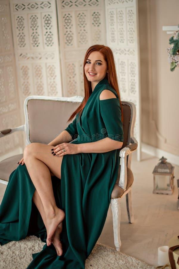 Porträt eines schönen Lächelnmädchens in einem grünen eleganten Abendkleid lizenzfreie stockfotografie