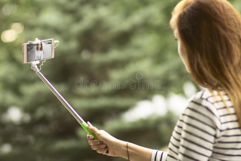 Porträt eines schönen Mädchens, das ein Foto für ein Soziales Netz in einem Stadtpark auf einem Smartphone unter Verwendung eines stockfotografie