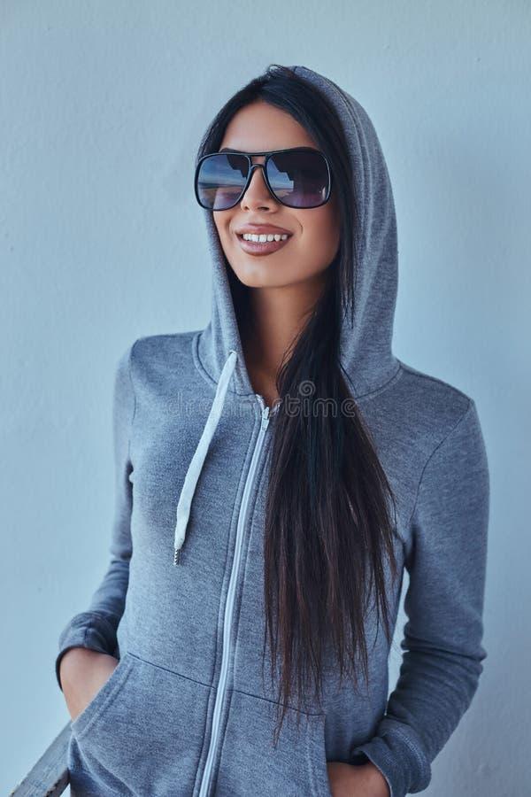 Porträt eines schönen Mädchens, das einen grauen Hoodie und Sonnenbrille trägt, hält Hände in den Taschen und lächelt und betrach lizenzfreie stockbilder