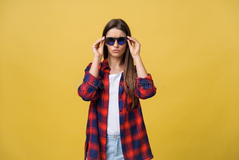Porträt eines schönen Mädchens in den runden Gläsern auf einem gelben Hintergrund im Studio lizenzfreie stockbilder