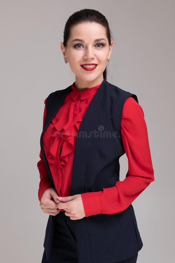 Porträt eines schönen Mädchens in der hellen Geschäftskleidung lokalisiert auf einem hellen Hintergrund stockbilder