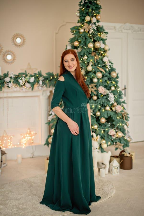Porträt eines schönen Mädchens in einem grünen Abendkleid am Hintergrund eines Baumweihnachten lizenzfreies stockfoto