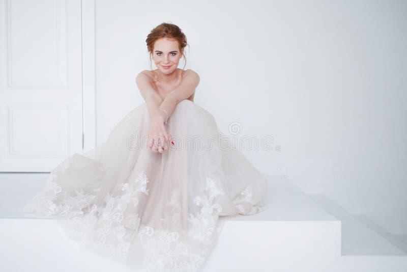 Porträt eines schönen Mädchens in einem Hochzeitskleid Braut im luxuriösen Kleid, das auf dem Boden sitzt stockfoto