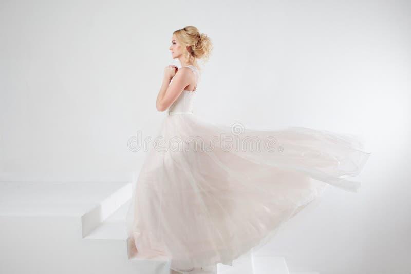 Porträt eines schönen Mädchens in einem Hochzeitskleid Konzept der Braut gehend in Richtung zum zukünftigen Glück, fliegender Roc stockfoto