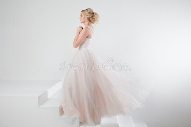 Porträt eines schönen Mädchens in einem Hochzeitskleid Konzept der Braut gehend in Richtung zum zukünftigen Glück, weißer Hinterg stockfotografie