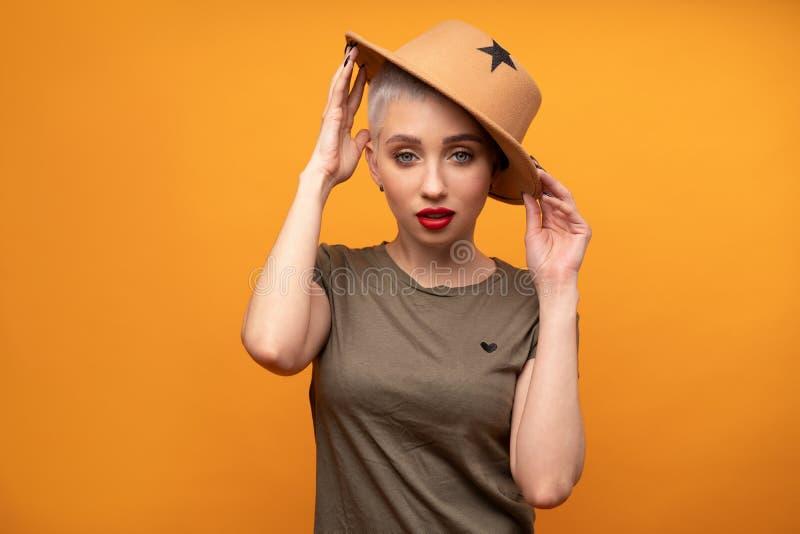 Porträt eines schönen Mädchens in einem Hut mit einem Rand im Studio auf einem orange Hintergrund lizenzfreie stockfotografie