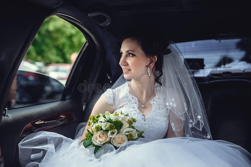 Porträt eines schönen Mädchens im Auto Die Braut hält einen Heiratsblumenstrauß in ihren Händen und in Blicken an der Straße durc lizenzfreies stockfoto